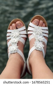 Feet of a young white caucasian female wearing very feminine sandals showing her toes. No nail polish. The shoes are white strap sandals with white leather flowers on them. Sea in the background.