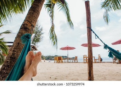 Feet of a young woman in hammock on the beach under the tree. Copy Space.