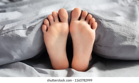 Feet of young woman lying in bed under blanket, closeup