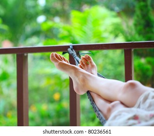 Feet of a young woman lying in hammock in a garden
