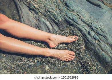 The feet of young woman resting in a rock pool
