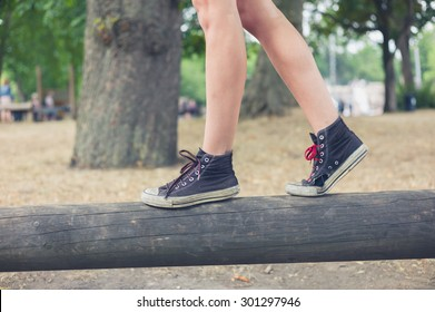The feet of a young woman as she is walking on a wooden beam outside in the park