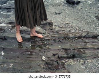 The feet of a young woman as she is walking on some rocks in the water on the shore