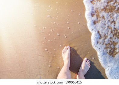 Feet of a young woman touching water on tropical beach in sunny summer day. Vacation holidays concept. Top view. Copy space.