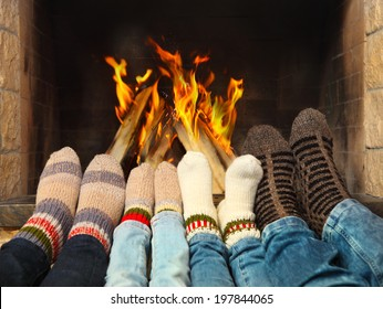 Feets of a family wearing woolen socks warming near the fireplace