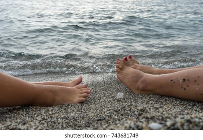 Feets relaxing at the beach in the water.