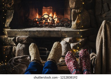 Feets in woolen knitted socks near fireplace