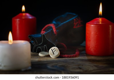 The Fehu rune is made ash tree trunk on a background of candles and a rune bag with a bokeh effect on a dark background
