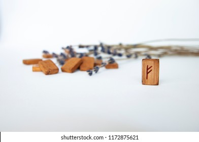Fehu. Scandinavian runes. Wooden runes on a table on a white background.