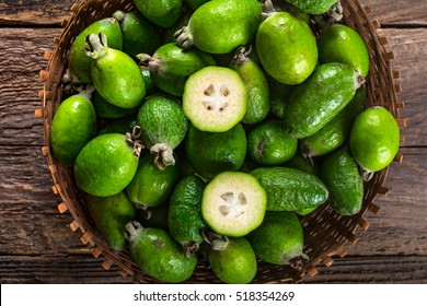 Feijoa fruits in wicker basket on wooden table