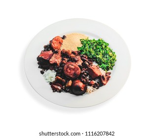 Feijoada, typical Brazilian cuisine. Feijoada on a white dish with white rice, black beans, sausage, pork meat, bacon, braised couve and manioc flour. Isolated on white.