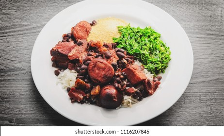 Feijoada, typical Brazilian cuisine. Feijoada on a white dish with white rice, black beans, sausage, pork meat, bacon, braised couve and manioc flour. Wooden table background.