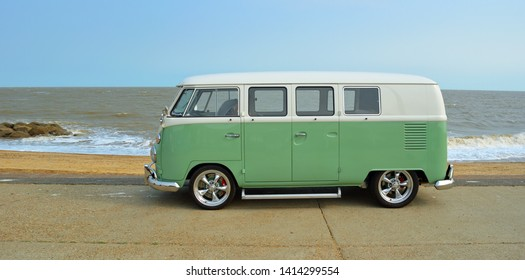 FELIXSTOWE, SUFFOLK, ENGLAND - AUGUST 27, 2016: Classic Green and white  VW Camper Van parked on Seafront Promenade. beach and sea in the background