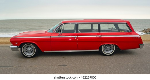 FELIXSTOWE, SUFFOLK, ENGLAND - AUGUST 27, 2016: Classic Red Chevrolet Impala Station Wagon parked on seafront promenade.