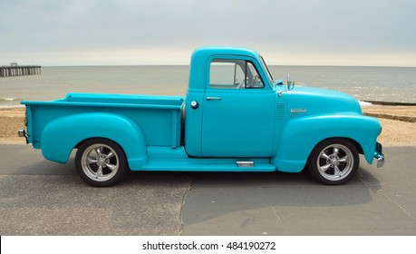 FELIXSTOWE, SUFFOLK, ENGLAND - AUGUST 27, 2016: Classic Light Blue  Chevrolet 3100 pickup truck on seafront promenade with sea in background