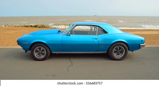 FELIXSTOWE, SUFFOLK, ENGLAND - AUGUST 27, 2016: Classic Blue Pontiac Firebird motor car  parked on seafront promenade.