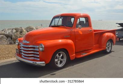 FELIXSTOWE, SUFFOLK, ENGLAND - AUGUST 29, 2015: Classic Bright Orange Chevrolet pickup truck on Felixstowe seafront.