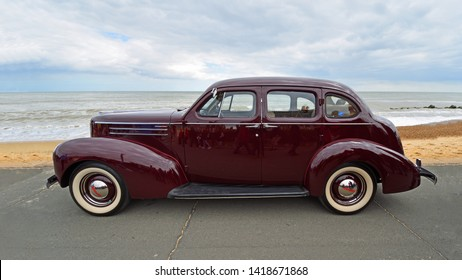 FELIXSTOWE, SUFFOLK, ENGLAND - MAY 05, 2019: Classic Dark Red Studebaker  motor car parked  on seafront promenade beach and sea in background.