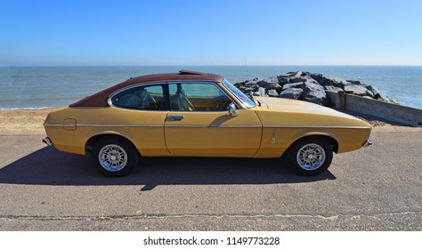 FELIXSTOWE, SUFFOLK, ENGLAND -  MAY 06, 2018: Classic Gold 2.0 Litre Ford Capri Ghia Motor Car Parked on Seafront Promenade.