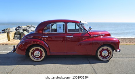 FELIXSTOWE, SUFFOLK, ENGLAND -  MAY 06, 2018: Classic Red 1953 Morris Oxford Motor Car Parked on Seafront Promenade.