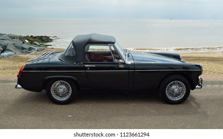FELIXSTOWE, SUFFOLK, ENGLAND -  MAY 07, 2017: Classic  Black  MG Midget  Car  parked on seafront promenade with sea in background.