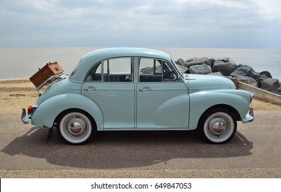 FELIXSTOWE, SUFFOLK, ENGLAND -  MAY 07, 2017: Classic Light Blue Morris Minor with picnic basket parked on seafront promenade.