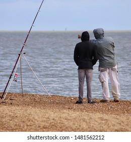 Felixstowe, Suffolk, UK - 18 August 2019: Bright summer Sunday afternoon. Fishermen on the beach at Landguard Point.