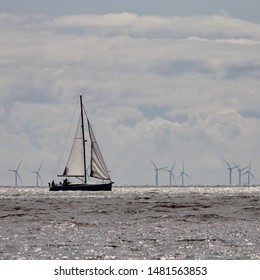 Felixstowe, Suffolk, UK - 18 August 2019: Bright summer Sunday afternoon. Sailing dinghy heading for harbour. Gunfleet Sands wind farm is visible in the distance.