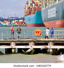 Felixstowe, Suffolk, UK - 18 August 2019: Bright summer Sunday afternoon. People on a jetty dwarfed by container ships docked at the port of Felixstowe.