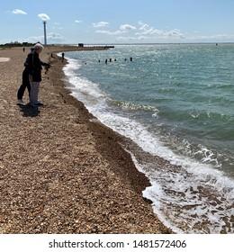Felixstowe, Suffolk, UK - 18 August 2019: Bright summer Sunday afternoon. Peopleon the shingle beach at Landguard Point.