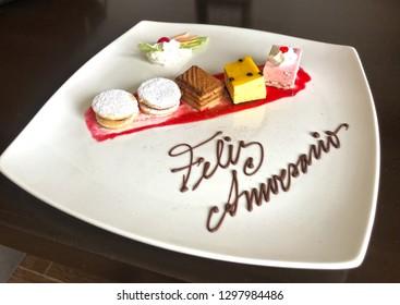 'Feliz aniversario' little colorful gourmet desserts as anniversary gift