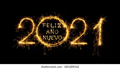 Feliz Ano Nuevo 2021. Creative lettering Happy New Year 2021 Spanish language written sparkling sparklers isolated on black background. Beautiful Glowing overlay template for holiday greeting card.