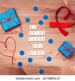 Feliz dia del padre that means happy fathers day  words made of wooden blocks with blue gift boxes and red hearts on wooden background. Happy fathers day greeting card, holiday flat lay