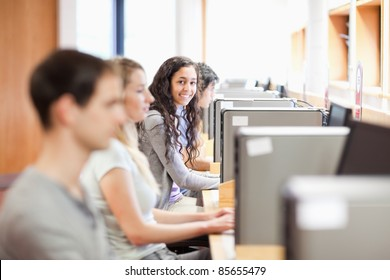 Fellow students in an IT room with the camera focus on the background