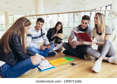 Fellow students sitting on floor in campus and preparing together for exams