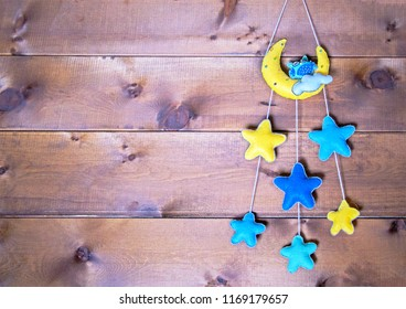 Felt baby mobile on wooden background. Soft toys: sleeping owl on moon with cloud & stars.