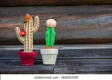 A  felt cactus toys Cowboy with hat and lady are on the old wooden texture background.  Copy space.