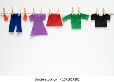Felt clothes hanging on rope on white background. Art craft creative concept with empty space for text.