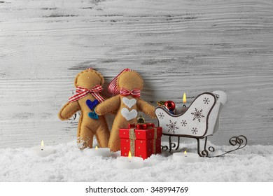 Felt  dolls with Santa sleds, candles and toys in a snow over wooden background, still life