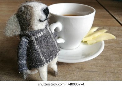 felt figure of a dog and a cup of coffee on a wooden table