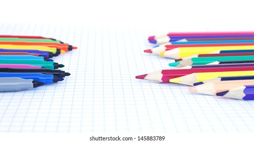 Felt pens and pencils  opposite each other on the notebook's sheet