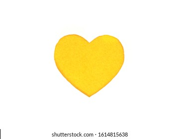 Оne felt yellow heart on a white isolated background. Stock photo for the day of St. Valentine with empty space for your text. For web, print, postcards and wallpaper.