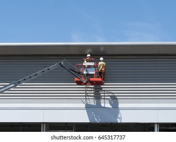 Feltham, Middlesex, England - May 22, 2017: construction workers on mobile access platform installing on cladding to new commercial warehouse development