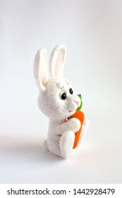 Felting toy small white rabbit with carrot isolated on white background. Cute needle felded eco-frendly toy