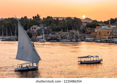 Felucca boat sailing on the Nile river at sunset in Aswan, Egypt