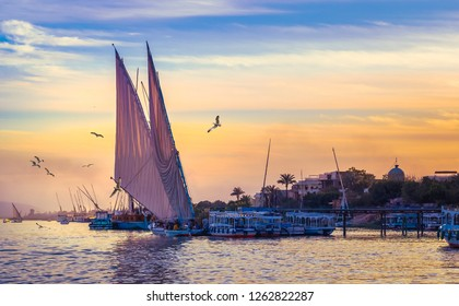 Felucca at sunset - voyage on sail vessel on the Nile river, romantic cruise and adventures in Egypt. Traditional egyptian sailboats and fisher boats on a pier, riverside view.