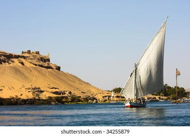 a feluka on the nile river in Egypt, in the background an old housing area on the hill of desert sand