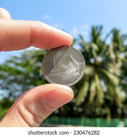 Femail fingers holding one rupee coin on the green palms background. Personal finance concept. Thumbs up.