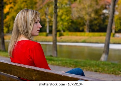 female absorbed in thought sitting on a bench in park