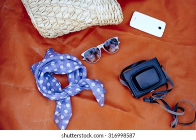 Female accessories: bag, scarf, sunglases, smartphone and came